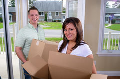 Moving House. You Couple Moving Into A New Home, Unpacking Cardboard Boxes Royalty Free Stock Photography