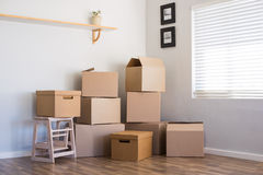 Moving house and boxes. Stack of cardboard boxes in an empty room. Pile of carton boxes on the floor in an empty apartment. Stack of moving boxes in new house stock photo