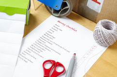 Moving House Checklist. A house moving checklist on a table, surrounded by labels, packaging tape roller, scissors, red marker pen, a ball of string and a sealed Royalty Free Stock Image