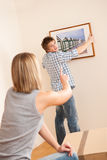 Moving house: Couple hanging picture on wall stock image
