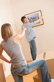 Moving house: Couple hanging picture on wall Stock Photo