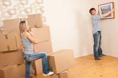 Moving house: Couple hanging picture on wall Stock Photos