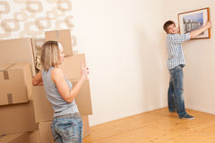 Moving house: Couple hanging picture on wall Stock Photography