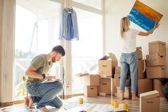 Moving house. Couple hanging picture on wall in new home stock photos