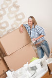 Moving house: Happy woman with box. Holding cup of coffee in new home Royalty Free Stock Photos