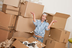 Moving house: Happy woman unpacking box. In new home, kitchen, pots and pans Royalty Free Stock Photo