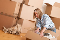 Moving house: Happy woman unpacking box. In new home, kitchen, pots and pans Royalty Free Stock Photos