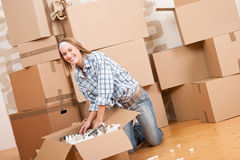 Moving house: Happy woman unpacking box Royalty Free Stock Photos