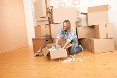 Moving house: Happy woman unpacking box. In new home, kitchen, pots and pans Stock Photography