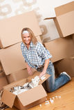 Moving house: Happy woman unpacking box. In new home, kitchen, pots and pans Stock Photo