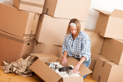 Moving house: Happy woman unpacking box. In new home, kitchen, pots and pans Stock Images