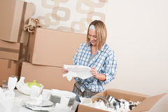 Moving house: Happy woman unpacking dishes. Moving house: Happy woman unpacking kitchen dishes in new home Royalty Free Stock Images