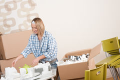 Moving house: Happy woman unpacking dishes. Moving house: Happy woman unpacking kitchen dishes in new home Stock Image