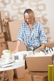 Moving house: Happy woman unpacking dishes. Moving house: Happy woman unpacking kitchen dishes in new home Royalty Free Stock Image
