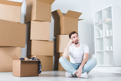 Moving in house. Man dreams sitting on the floor in the background box. Stock Photos