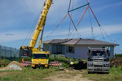 Moving house New Zealand style. Motueka, Tasman/New Zealand - December 7, 2018: A house that has been sawn in two and moved to its new address being unloaded stock photography