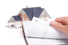 Moving house planning. Concept. Model of house and man browse through personal organizer stock image