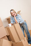 Moving house: Woman with box in new home. Having cup of coffee Stock Photos