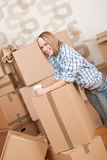 Moving house: Woman with box in new home. Having cup of coffee Royalty Free Stock Image