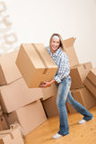 Moving house: Woman holding big carton box. In new home Stock Photo