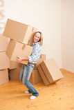 Moving house: Woman holding big carton box. In new home Royalty Free Stock Photography