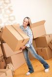 Moving house: Woman holding big carton box. In new home Royalty Free Stock Images