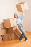 Moving house: Woman holding big carton box. In new home Stock Image