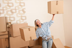 Moving house: Woman holding big carton box. In new home Royalty Free Stock Photo
