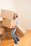 Moving house: Woman holding heavy carton box. Moving house: Woman holding big carton box in new home Royalty Free Stock Photo