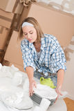 Moving house: Woman unpacking box. With kitchen dishes, plates Royalty Free Stock Photos
