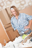 Moving house: Woman unpacking box. With kitchen dishes, pots and pans Royalty Free Stock Photo
