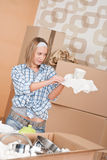 Moving house: Woman unpacking box. With kitchen dishes, pots and pans Stock Photo