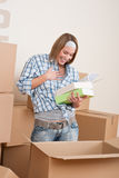 Moving house: Woman unpacking box with book. In new home Royalty Free Stock Photo