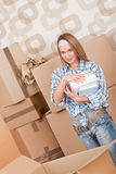 Moving house: Woman unpacking box with book. In new home Stock Image