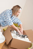 Moving house: Woman unpacking box with pot. Moving house: Woman unpacking box  with kitchen dishes, pots and pans Royalty Free Stock Photography