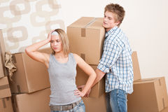 Moving house: Young couple with box. In new home Royalty Free Stock Images