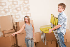 Moving house: Young couple with box and chair. Woman pointing Royalty Free Stock Photo