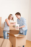 Moving house: Young couple with box in new home. New house: Young couple with box in new home unpacking book Royalty Free Stock Images