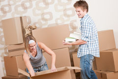 Moving house: Young couple with box in new home. New house: Young couple with box in new home unpacking book Royalty Free Stock Photos