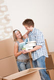 Moving house: Young couple with box in new home Stock Photo