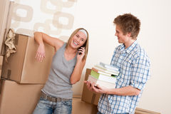 Moving house: Young couple with box in new home. New house: Young couple with box in new home unpacking book, woman with mobile phone Stock Photography