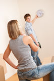 Moving house: Young couple hanging clock on wall Stock Photography