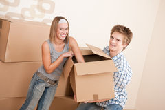 Moving house: Young couple moving box, unpacking. New house: Young couple moving box, unpacking in new home Royalty Free Stock Images