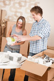 Moving house: Young couple unpacking dishes Royalty Free Stock Images