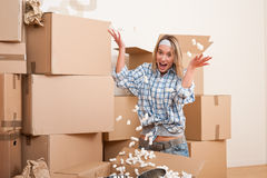 Moving house: Young woman having fun. Unpacking box Royalty Free Stock Photo