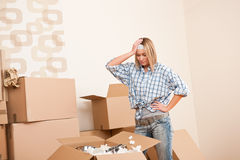 Moving house: Young woman unpacking box. With kitchen dishes Stock Photo