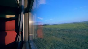 Moving inside the train cabin across the fields. Travelling by train concept.