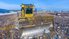 Moving landfill truck. Enviromet pollution concept. A landfill compactor moving in front view on its straight blade stock video footage