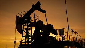 Moving large pumpjack is pumping petroleum from ground in sunset time, view against orange sky stock video footage