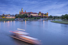 Moving lights on the river before castle in twilight time Stock Images